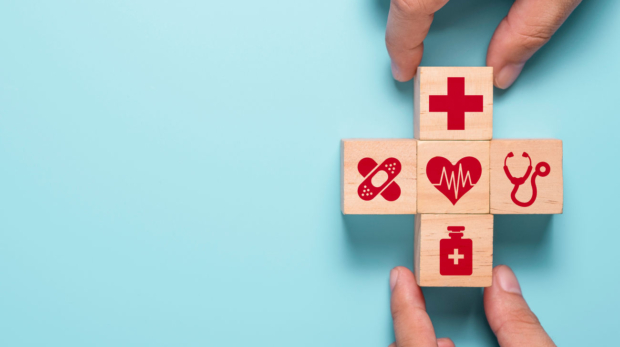 hand-putting-wooden-cubes-of-healthcare-medicine-and-hospital-icon-on-blue-table-health-care-insurance-business-and-investment