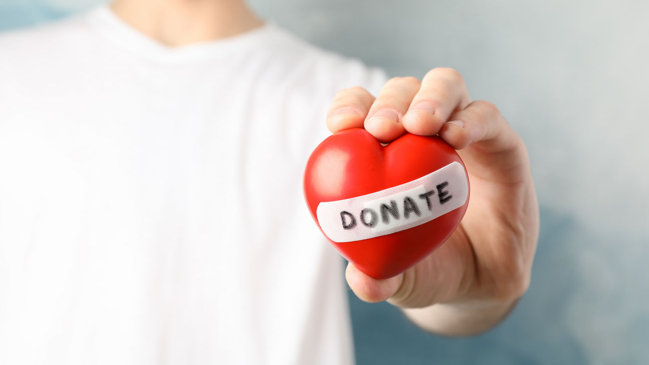 man-holds-heart-on-blue-space-close-up-health-care-organ-donation