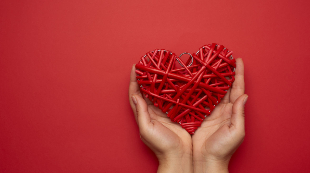 two-female-hands-holding-a-red-wicker-heart-love-concept-copy-space